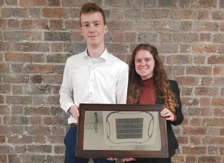 A young man and a young woman pictured against a brick wall. They are holding up a mirror-like device.