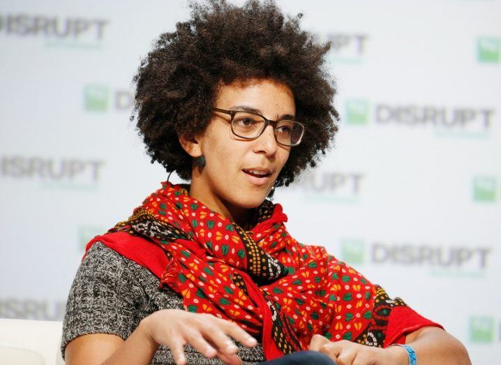 Dr Timnit Gebru wearing a red shawl and glasses speaking on stage behind a white background.
