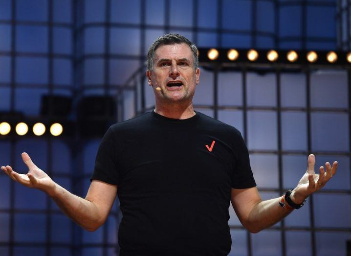 Ronan Dunne wearing a branded black Verizon t-shirt holding his hands out on stage.