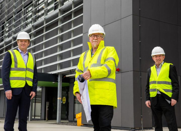 Three men stand a few feet apart in front of a large grey building. They are wearing high-vis jackets and hard hats.