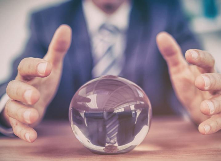 A man in a suit is sitting at a desk with his hands above a crystal ball as if he is making technology predictions.