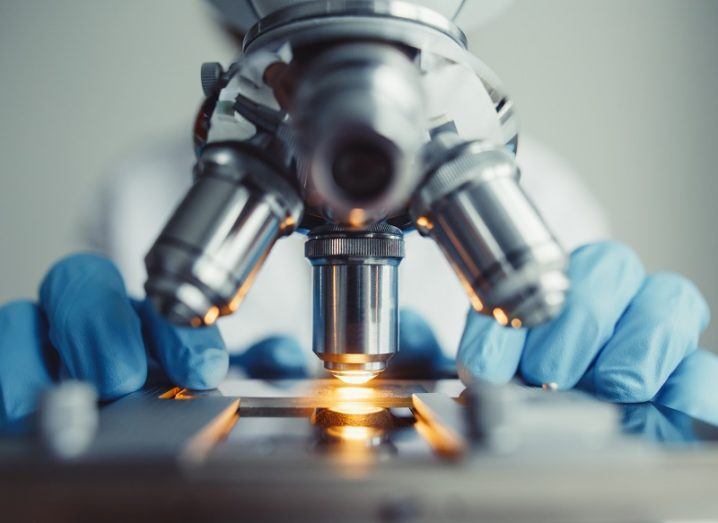 Close-up of a researcher wearing blue gloves operating a microscope.