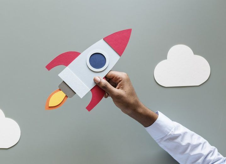 Hand holding a paper rocketship against a grey background.