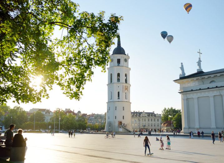 A square in an old European city on a sunny day. Around the square is a bell tower next to a neo-classical cathedral. Hot air balloons can be seen in the sky.