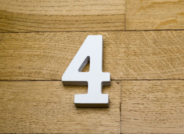 A white 3D number four on a wooden parquet floor.