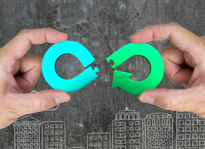 Hands holding puzzle pieces that, when connected, will form a circular economy loop.