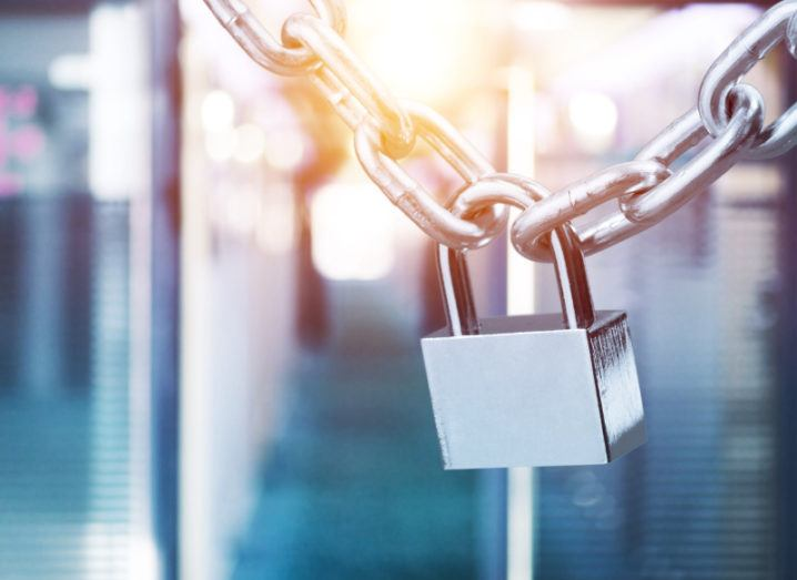 A silver padlock is on a chain against a blurred background.