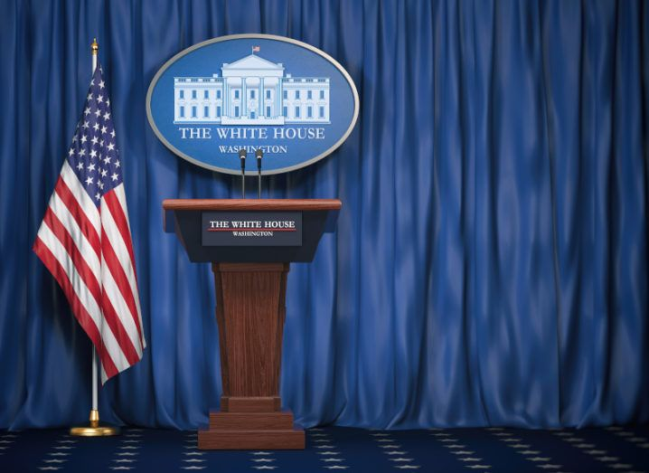 A podium staged for a briefing from the US president in the White House, with a blue curtain background and a US flag standing next to it.