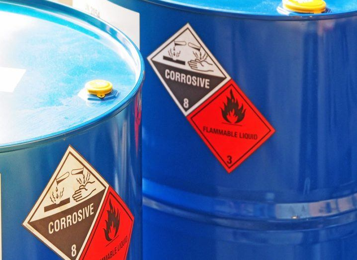 Blue, steel barrels with red and white warning labels on them.
