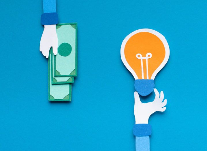 Paper cut-outs of one hand reaching out holding dollars and another holding a lightbulb, representing investment in an idea.