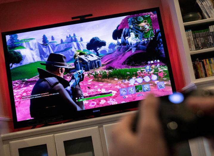 View from a game controller at a large TV screen in a living room showing a video game in play, with a character pointing a gun at a shack in a colourful mountain landscape.