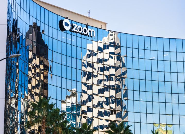 A large, curved glass building bearing the blue Zoom logo across the top floors.