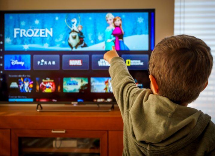 Child pointing to a TV with a streaming platform open.
