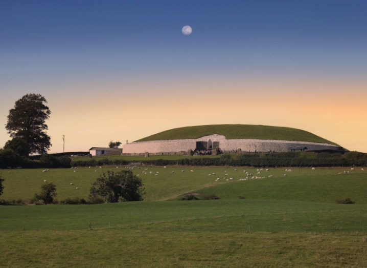 The expansive dome of the Newgrange passage tomb visible on the horizon at dusk, with the moon already visible in the darkening sky.