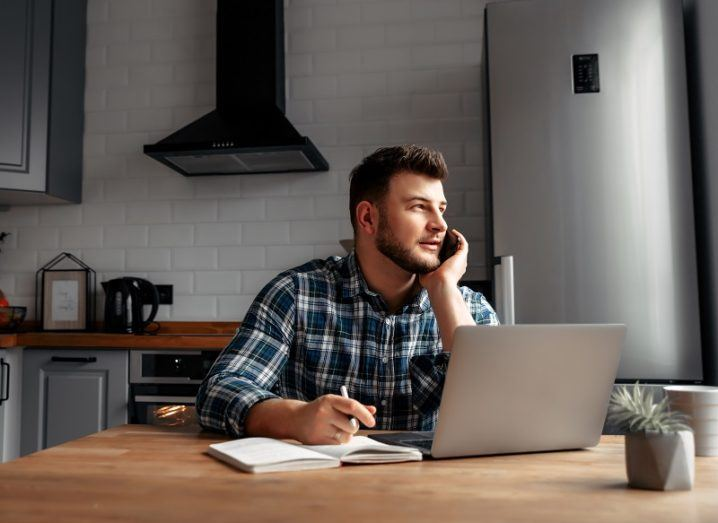 Man working from home at a laptop and on the phone in his kitchen.