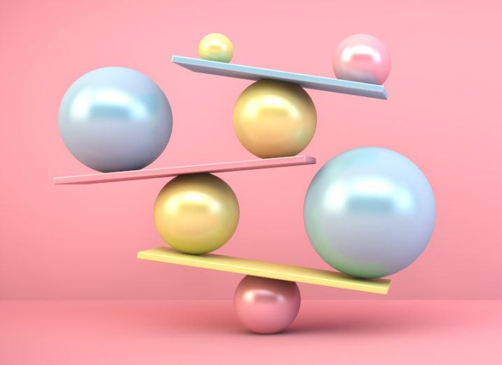 A colourful selection of balls and beams, all balanced atop one another against a soft pink background.