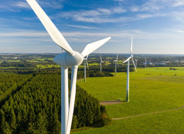 Photo of windfarms in green countryside against a blue sky.