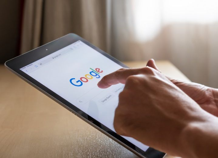 Hand using a tablet with Google search open.
