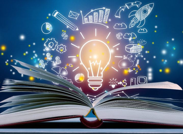 A book is lying open on a table, under an illustration of a lightbulb and other images relating to business and innovation.
