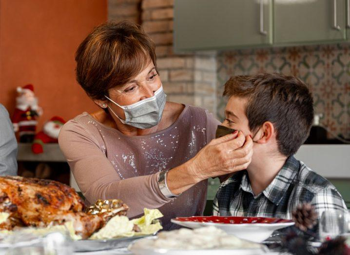 Woman wearing a face mask at a dinner table putting another mask on a boy.