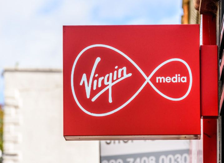 Virgin Media logo on a red signpost outdoors.