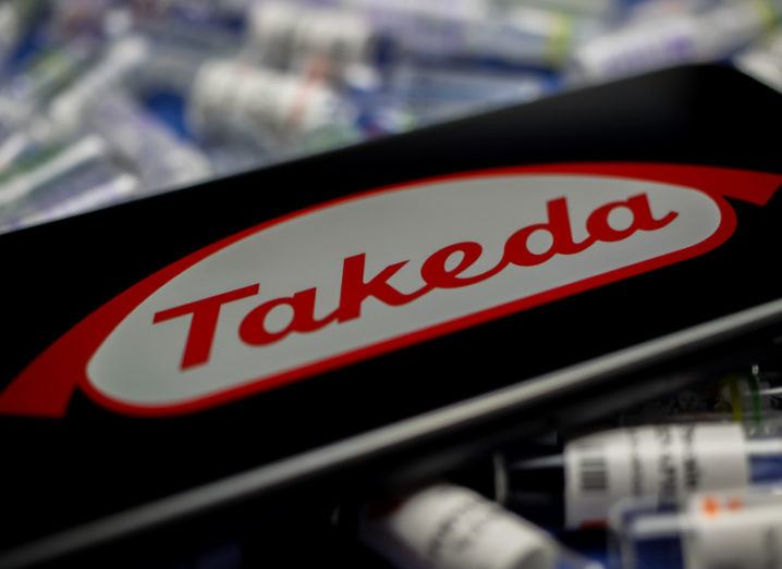 Takeda logo on a smartphone screen against packs of medicines.