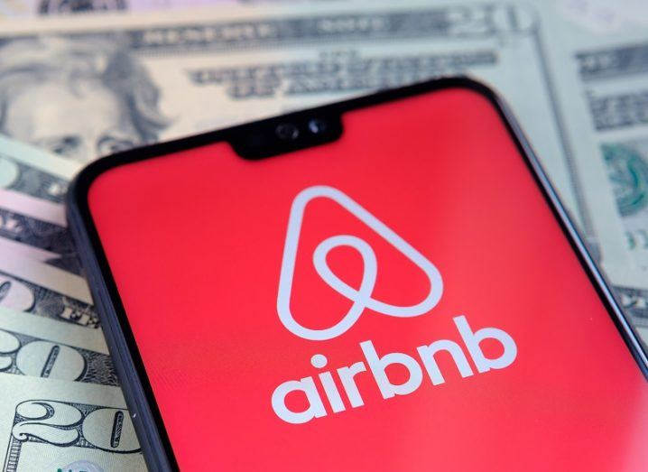 The Airbnb logo on a phone on top of dollar bills.
