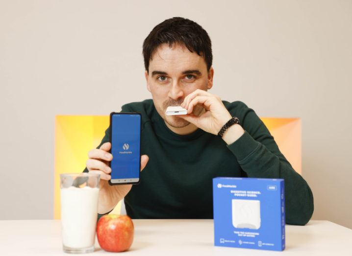 FoodMarble CEO blows into the company's Aire device, while holding a phone displaying the FoodMarble app. On the table in front of him is an apple and a glass of milk.
