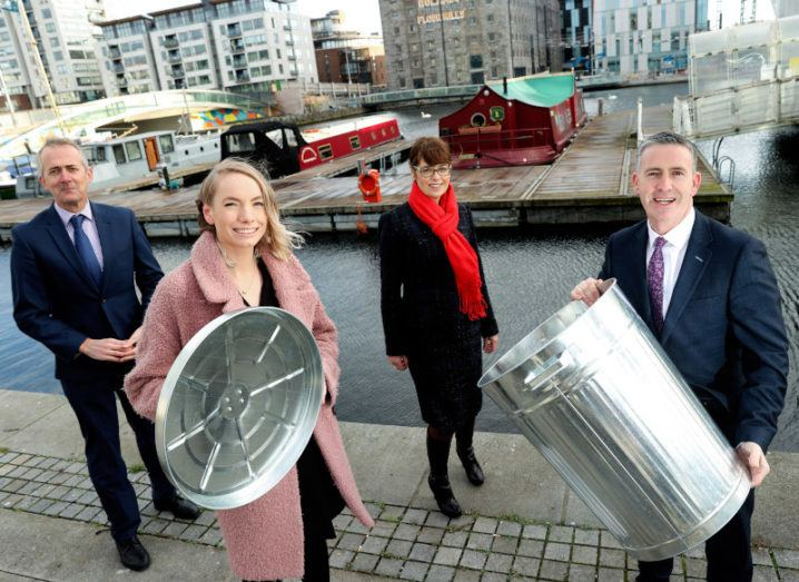 Two men and two women pictured in the Dublin docklands. The man and woman in the foreground are holding the lid and container of a large silver bin.