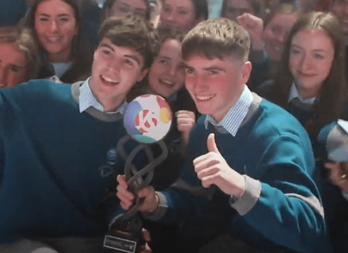 Cormac Harris and Alan O'Sullivan holding their BTYSTE 2020 trophy surrounded by students.
