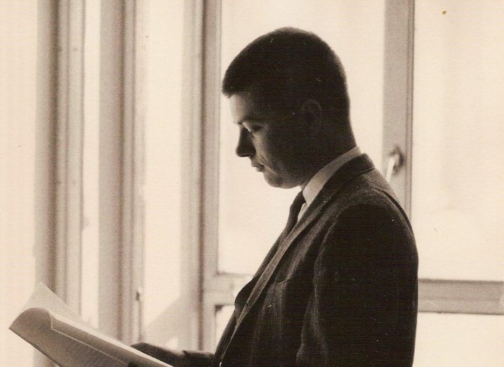 An old photograph of Bob Kerwin as a young man standing by a window and reading papers.