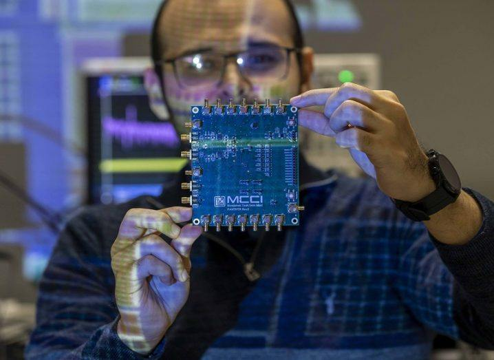 Gerardo Salgado of MCCI holding a semiconductor up in a dimly lit room.