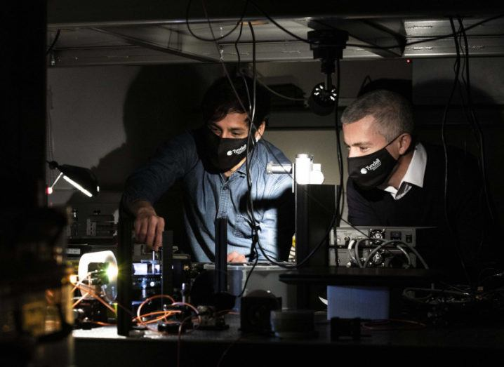 Two men work on electronics in a dark lab.