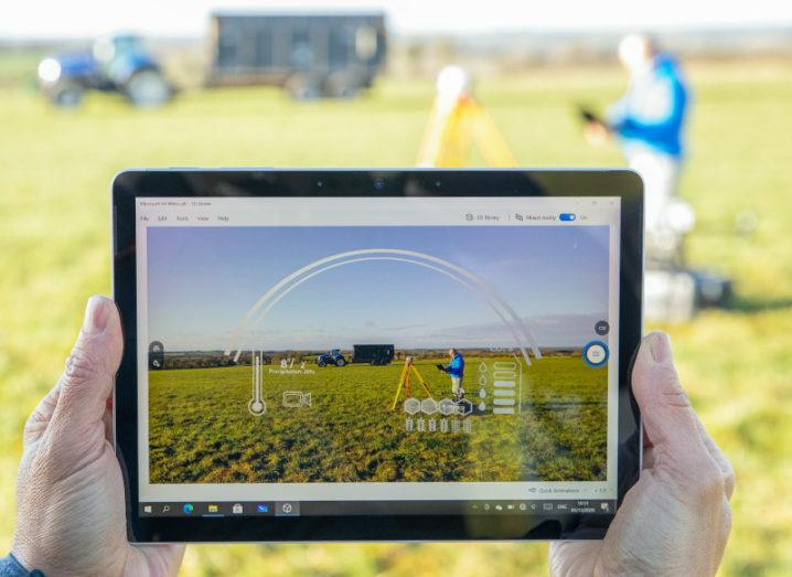 Hands hold a Microsoft device in front of a green field. On screen is an illustration of different information as a man stands in the field capturing data.