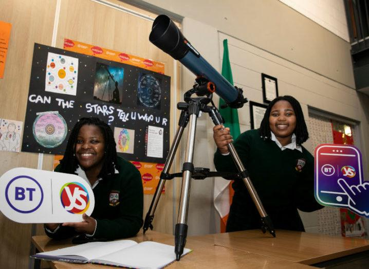 Two teenage girls in dark school uniforms stand holding a telescope and a BT Young Scientist poster. Behind them is a poster that says: 'Can the stars tell who you are?'