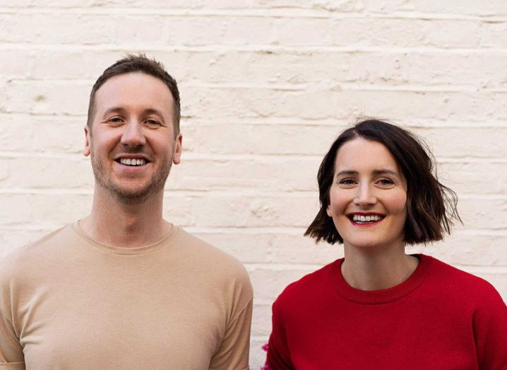 A man and a woman pictured smiling against a white brick wall.