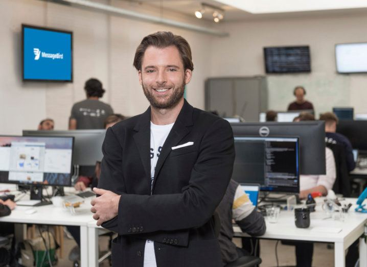 A man in a black suit jacket stands smiling with his arms folded in a busy office. Behind him, a screen displaying the MessageBird logo is on the wall.