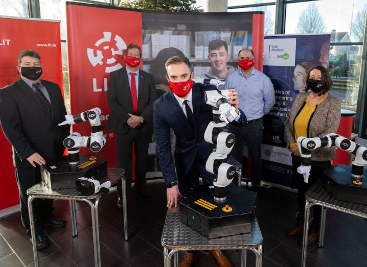 A group of people wearing face masks are pictured with three robotic arms at the launch of IDEAM in Limerick.