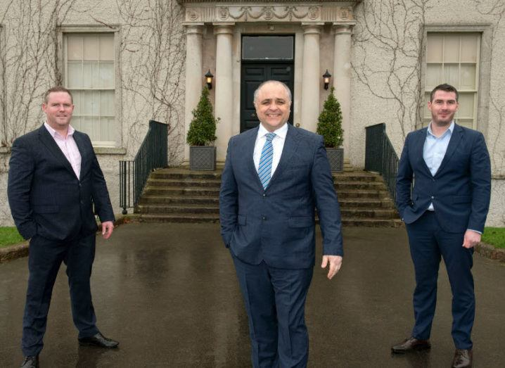Three men in dark suits stand a few metres apart in front of an off-white stone building.