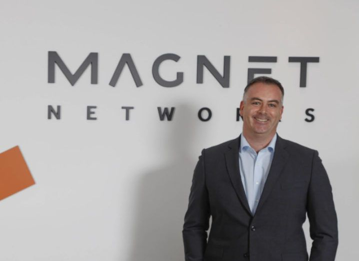 John Delves in a blue shirt and grey blazer stands smiling with his hands in his pockets in front of a Magnet Networks logo.