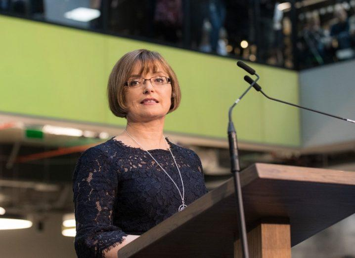 Cathriona Hallahan speaking at a podium against a green background.