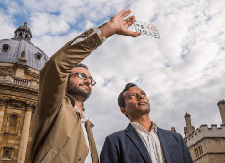 Dr Peiman Hosseini and Prof Harish Bhaskaran, co-founders of Bodle, are standing outdoors under a cloudy sky and looking up at a digital display.