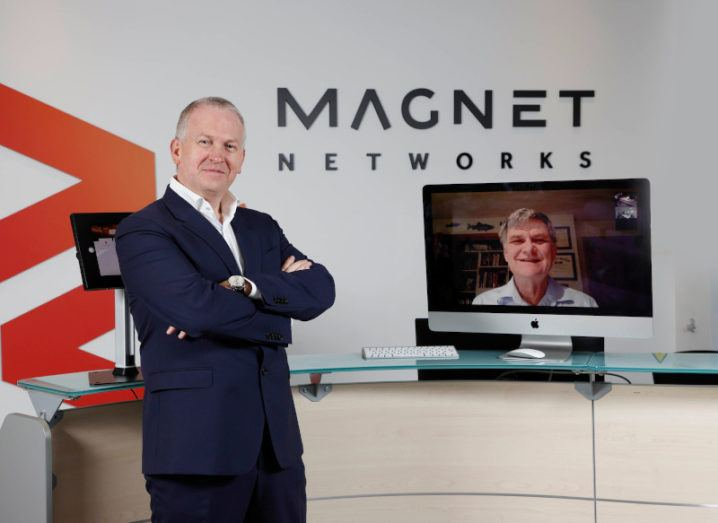 Speed Fibre Group CEO Peter McCarthy stands next to a screen hosting a video call to Ken Peterson. He is in a Magnet Networks office.
