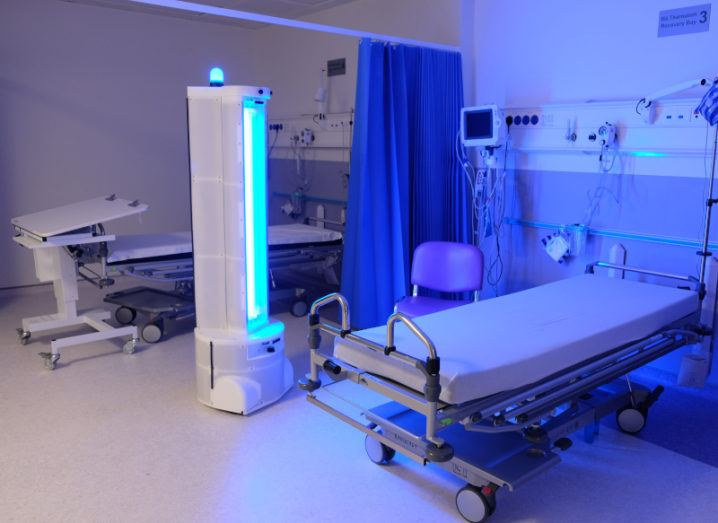 A tall robot beams an ultraviolet light into a hospital ward containing beds and other medical equipment.