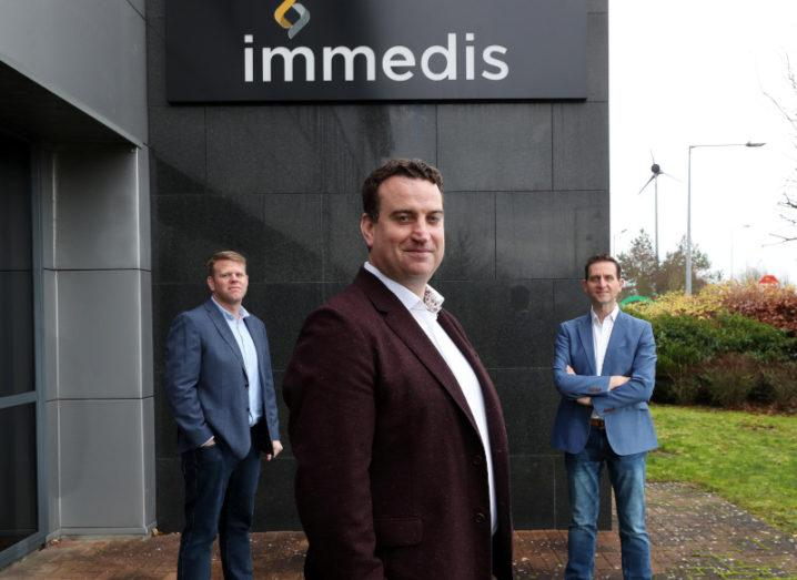 Three men in suits stand outside of the Immedis office.