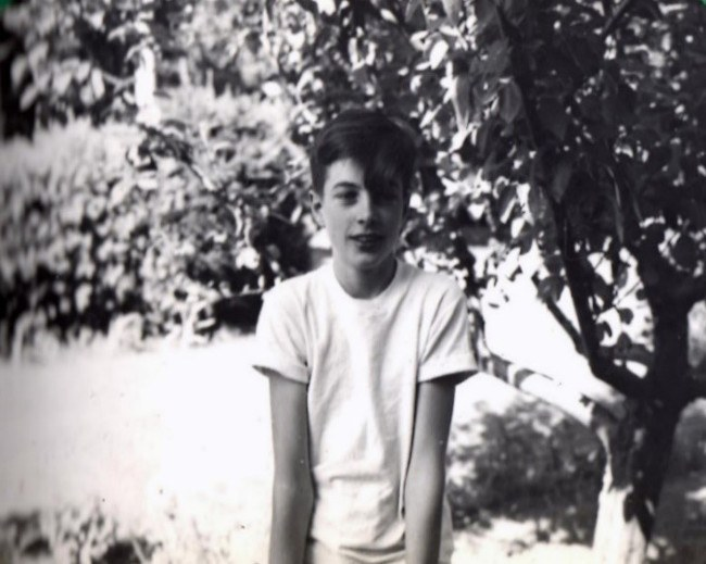 Black and white photo of Bob Kerwin as a young boy out in the sunshine, surrounded by foliage.