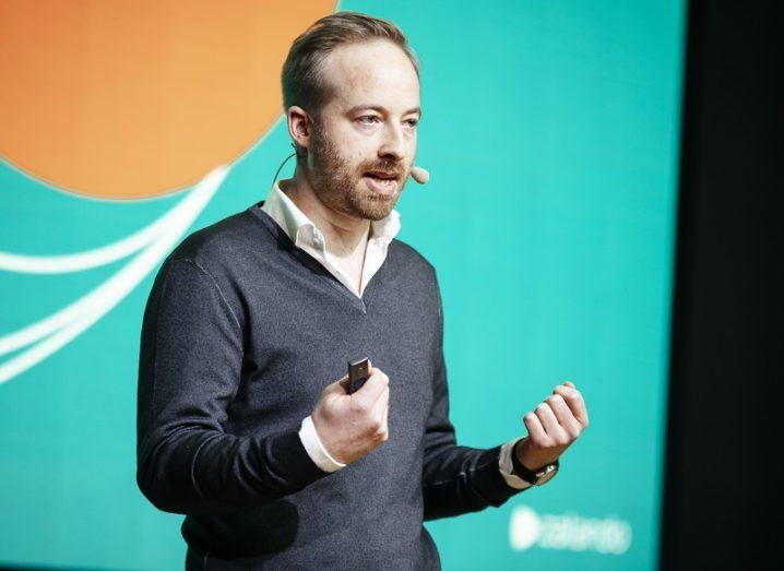 Rubin Ritter speaking on stage wearing a grey jumper in front of a green and orange wall.