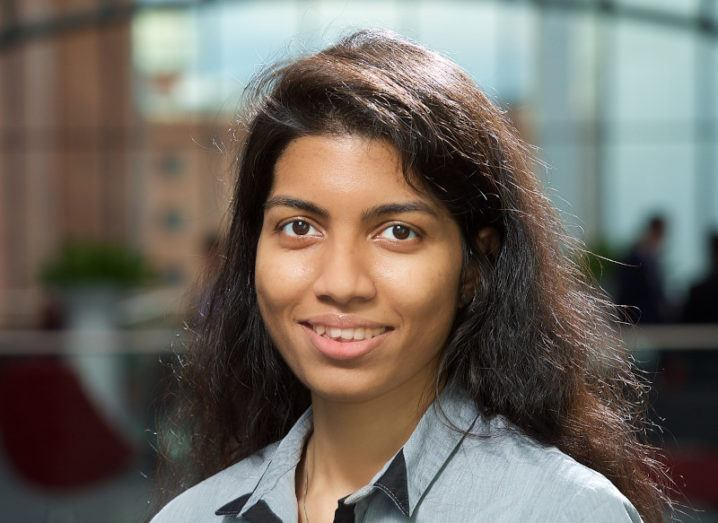 A young woman, Deva Senevirathne, smiles at the camera. Behind her is an out-of-focus office.