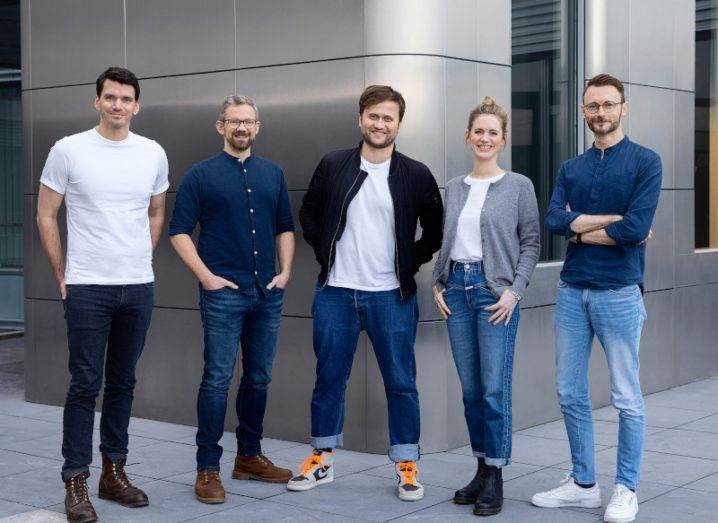 The Taxdoo team, comprising four men and one woman wearing casual clothing, stand in a line in front of a grey steel building.