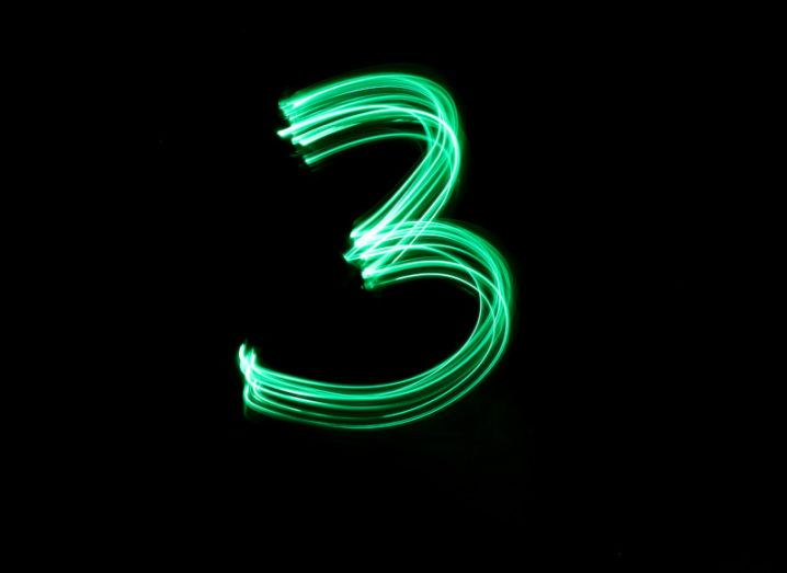 A long-exposure photo of a neon green light stroke, which etches out the number three against a black background.
